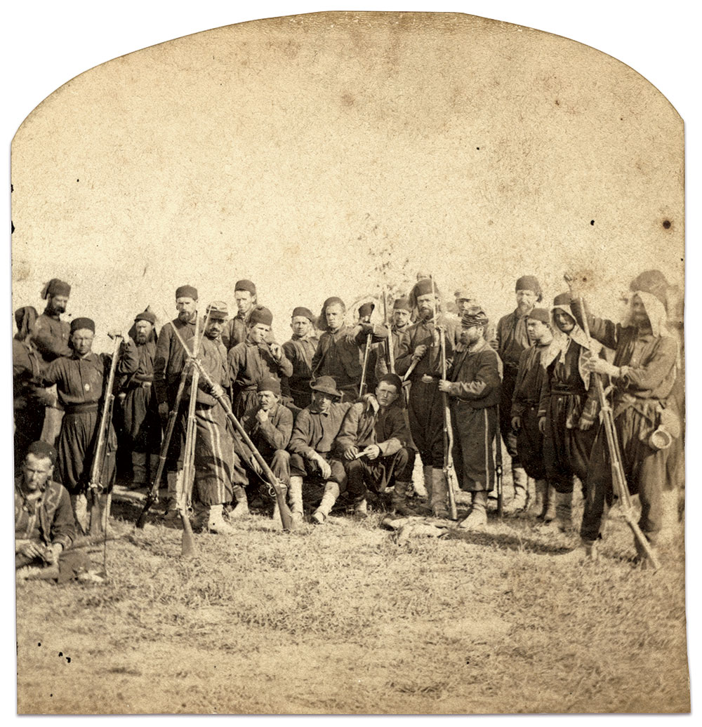 OFF DUTY: Most of these men wear uniforms probably supplied by Devlin, Hudson & Co., which included jackets with red worsted tombeau and trefoil trim. Two men, one seated on the ground at the extreme left and another standing second from right, wear jackets with different, lighter-colored zig-zag trim on the chest and matching cuff decoration. These may be examples of the 209 uniforms supplied by William Seligman & Co. Two other men, possibly non-commissioned officers, wear forage caps and have seam stripes on their breeches. Several wear white havelocks underneath their fezzes, while the man at extreme right is missing his white canvas leggings.