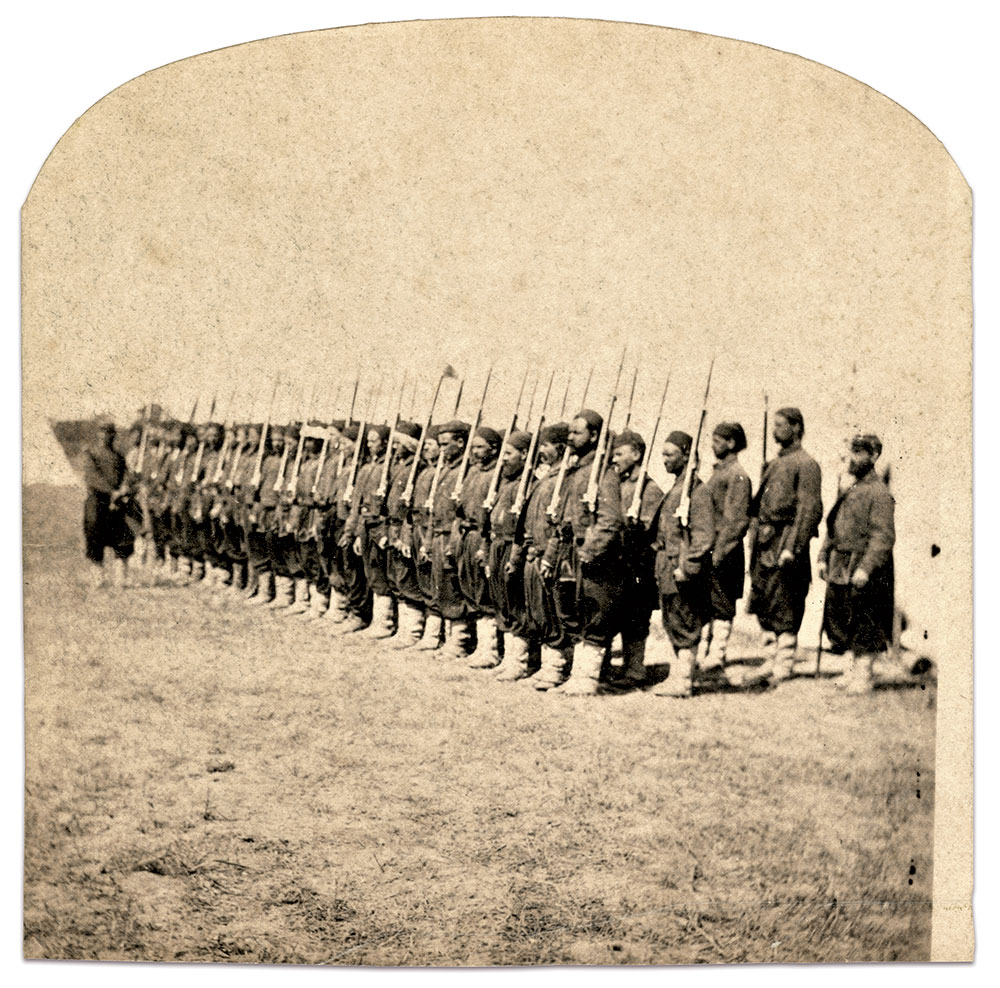 AT DRILL: Only two men wear white turbans wrapped around their heads in this company parade. Another at the center is without canvas leggings. The non-commissioned officer at right appears supporting a general guide, or marker flag. These flags typically posted at each flank of the regiment to assist the field officers in maintaining a straight line of battle.