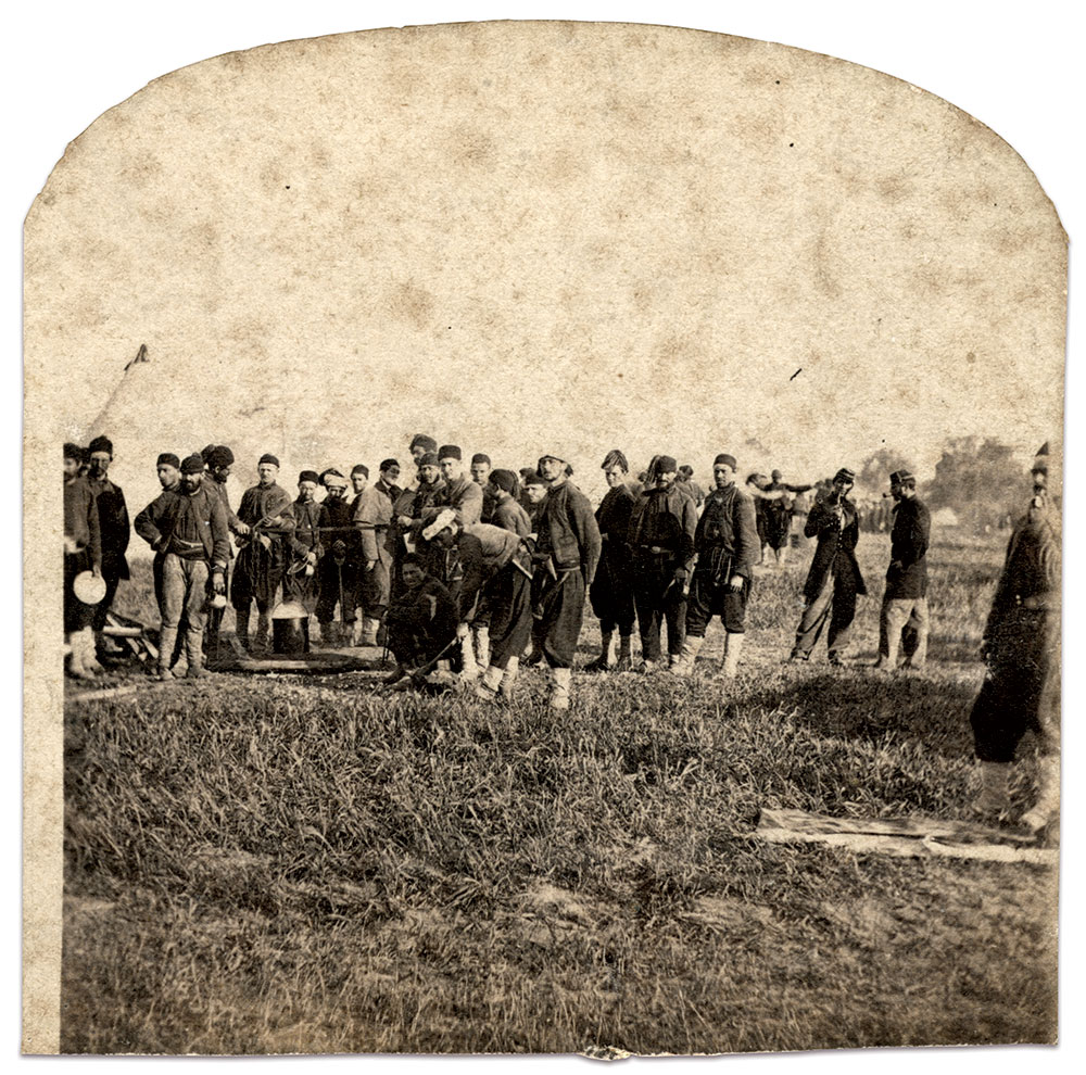 IN THE CHOW LINE: The Zouave at left wears sky-blue uniform pants tucked into white canvas leggings. Another proudly poses in the grey overcoat issued with their first uniform. White turbans again wrap around fezzes. Several men at the right demonstrate differing ways of sporting the tassel on the fez. One of these also wears his breeches outside his leggings.