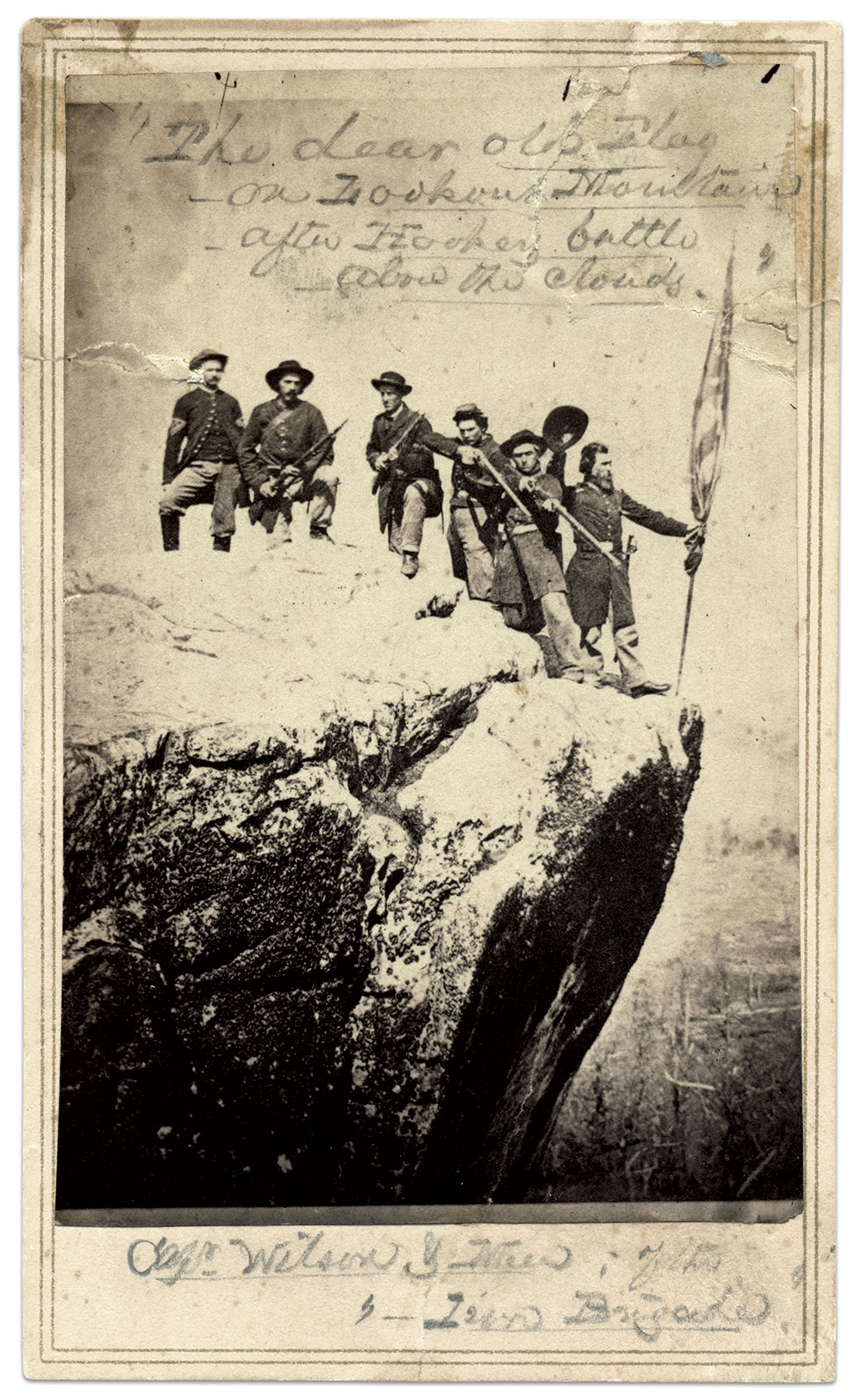 """""""The dear old Flag on Lookout Mountain after Hooker's battle above the Clouds"""" From the left: Sgt. Joseph Wagers, Pvt. Joseph Bradley, Sgt. Harris H. Davis, Pvt. William Witt, Sgt. James Wood, and Capt. John Wilson of the 8th Kentucky Infantry, a regiment in the Iron Brigade."""