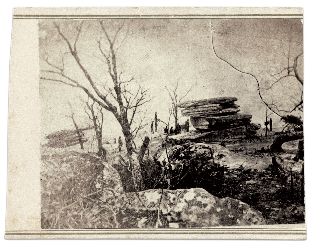 """Captured by the camera: Linn or an assistant appears to aim the camera lens at a soldier standing on the Point while other men gather near Umbrella Rock and out of the way of the photographer's view. Also of note is an inscription, """"Crest of Lookout,"""" which is etched into the negative over the rocks in the right foreground."""