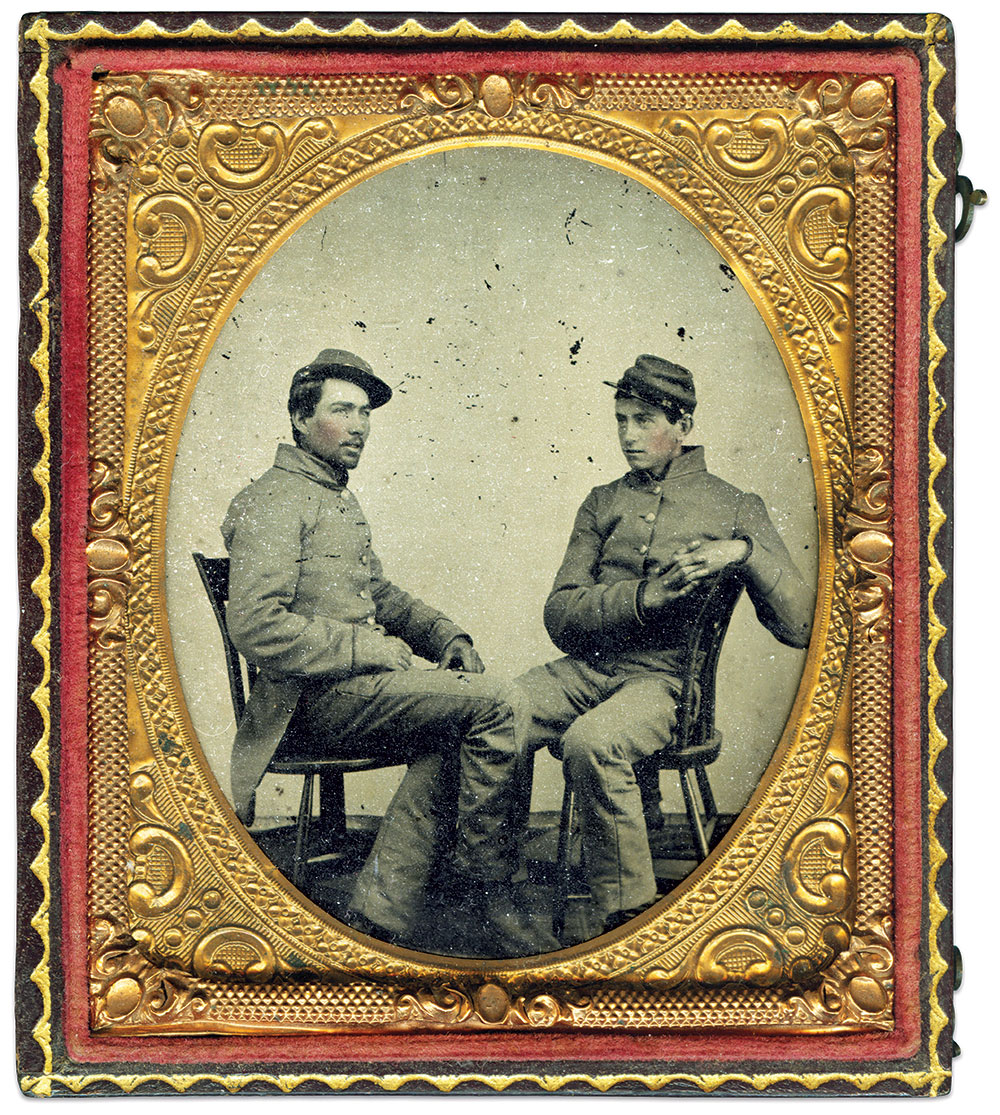 """These unidentified privates wear the gray dress uniform provided for both the 1st or 2nd New Hampshire infantries by the state quartermaster in May 1861. The man at left is clearly seated to show his """"spike-tail"""" coat to best advantage. Their chasseur-pattern caps had red bands, and high standing collars and closed cuffs were trimmed with narrow red cord. Trousers were plain gray. Sixth-plate ruby ambrotype by an anonymous photographer. Ron Field Collection."""