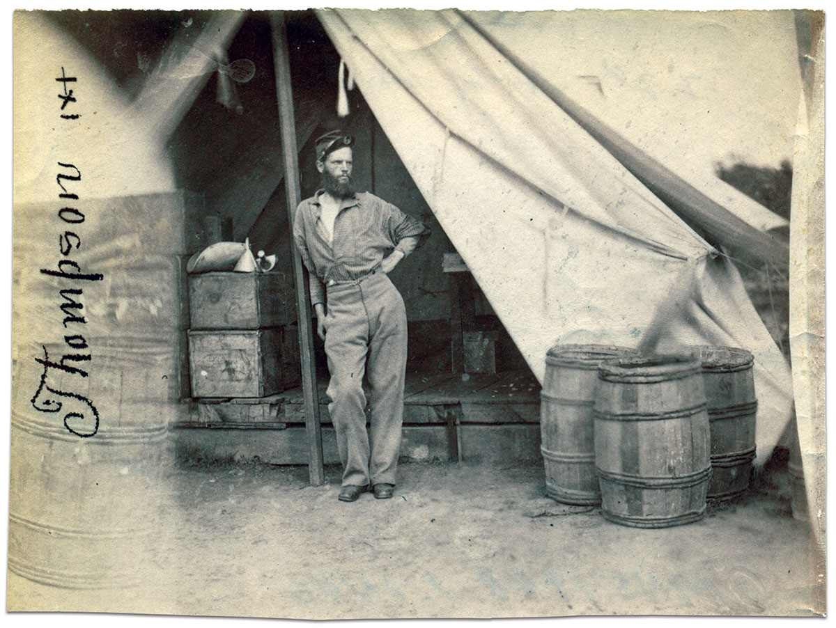 Commissary Sgt. John C. Thompson leans against the post of a tent filled with wood boxes and measuring cups. Originally a private in Company A, he was appointed commissary in July 1862.