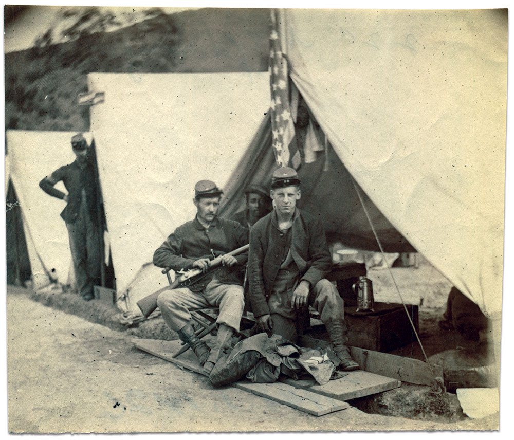 Pvt. George Sheppard of Company G knelt before his open backpack in front of a tent and below the Stars and Stripes. A stack of letters wrapped by ribbon is visible on top of the pack. He served on duty in Harpers Ferry for three months in 1862, and in Pennsylvania for a 30-day stint in 1863.