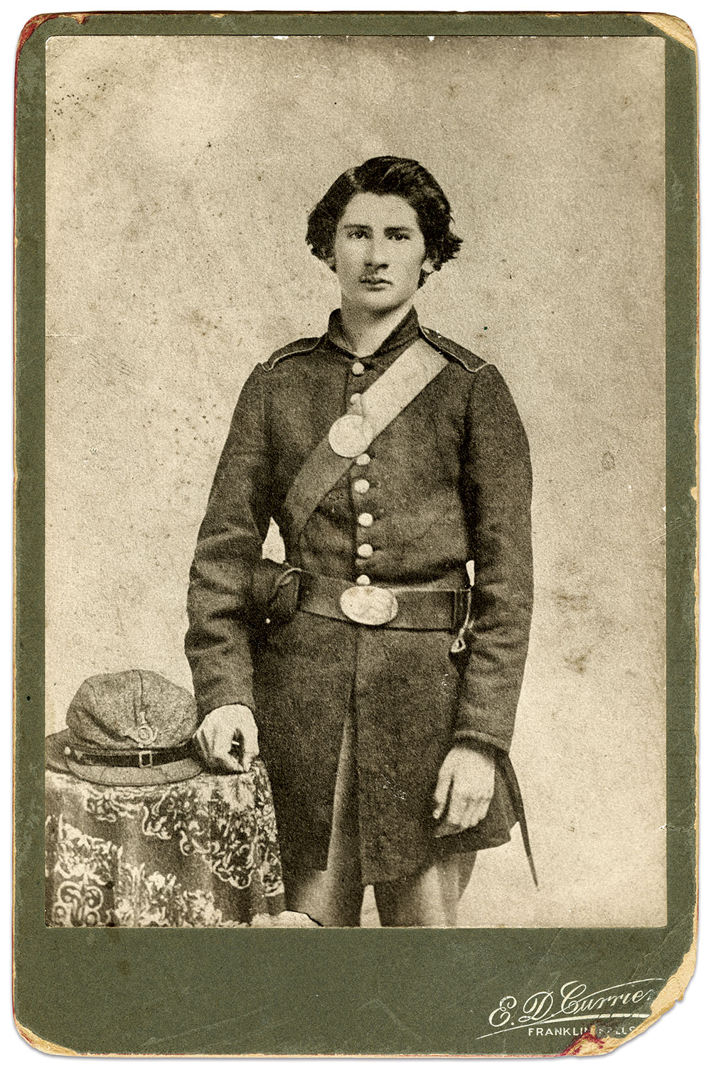 """Photographed in 1861, 19-year-old Pvt. Arthur H. Perkins of Company I, 5th New Hampshire Infantry wears an example of the frock coat of """"shoddy"""" flannel supplied to his regiment by merchant tailors Lincoln & Shaw of Concord. Placed carefully on the table by his side, his Havelock cap has pinned at its front a small looped horn insignia with regimental numeral """"5"""" inset and company letter """"I"""" above. The leather equipment for this regiment, including belts, cartridges boxes and cap pouches, was made by Solon S. Wilkinson, of Keene, N.H., who was reported in the Sentinel of that place on Oct. 17, 1861, to have """"employed from twenty to twenty-five hands in the work."""" Perkins was appointed second lieutenant on Nov. 1, 1863, and honorably discharged on Nov. 6, 1864, returning to his home in Danebury, N.H. Post-war cabinet card by Edward D. Currier of Franklin Falls, N.H. Ron Field Collection."""