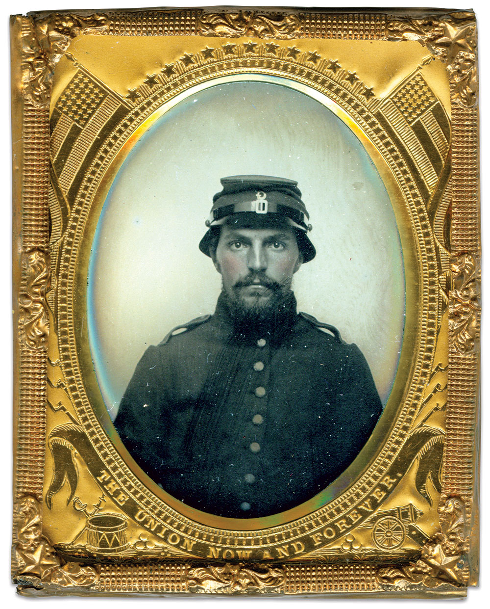 This unidentified private in Company G of the 6th or 8th New Hampshire infantry wears a modified version of the Havelock cap produced by Purinton & Ham. Possibly due to the unpopularity of the Havelock hats issued to the previous three regiments, this version was patterned after a more orthodox forage cap, but had a stiffened leather visor curved around its sides and rear. He also wears a frock coat made by Lincoln & Shaw, of Concord, which has a plain collar and cuffs, and shoulder straps edged with sky blue. Ninth-plate tintype by French & Sawyer of Keene, N.H. Ron Field Collection.