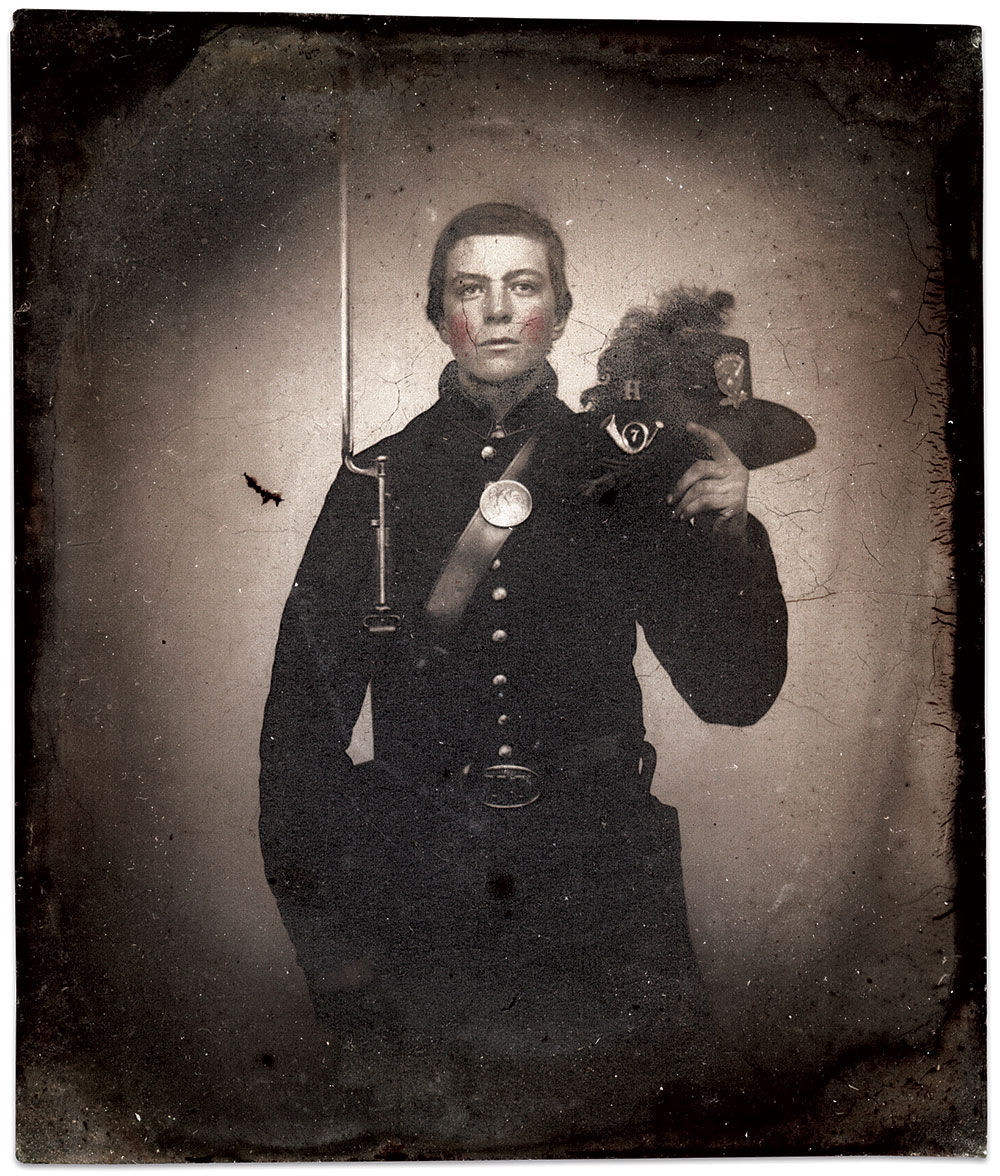 """Probably photographed at Manchester, N.H., this enlisted man of Company H of the 7th New Hampshire Infantry is either Albert F. or Alfred F. Hills, of Hollis, in Hillsborough County, N.H. He wears the uniform supplied to his regiment by the federal government that was largely based on U.S. Army regulations. Reminiscent of images of later regiments, he holds aloft his pattern 1858 dress or Hardee hat with black ostrich feather plume fastened to the right side and brim looped up on the left via a brass eagle device. The regulation brass infantry horn, with numeral """"7"""" set within the loop, and company letter """"H"""" above, is pinned to the front of the crown. His pattern 1851 frock coat is trimmed with sky-blue around collar and cuffs. He holds a Pattern 1853 Enfield rifle musket. Sixth-plate clear glass ambrotype by an anonymous photographer. Ron Field Collection."""