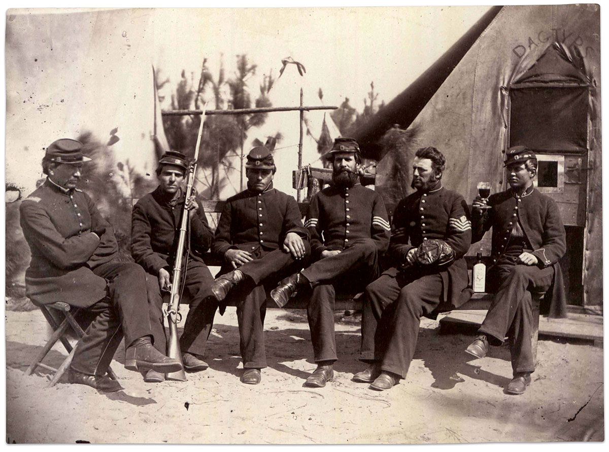 """Wearing dark blue frock coats and pants received on Jan. 9, 1862, five members of Company H of the 3rd New Hampshire Infantry pose in front of Henry P. Moore's """"Dagtyps"""" tent studio on Hilton Head Island, S.C. The identity of the sixth man, seated on the far right with glass and the company letter H attached to his collar and cap, is unknown. The five men are, from left to right: Lt. John F. Langley, J.F. Hunt, Pvt. Walter A. Lawrence, Sgt. Stephen S. Fifield, and 1st Sgt. Henry F. Hopkins. MOLLUS-Mass Civil War Photograph Collection, U.S. Army Heritage and Education Center."""