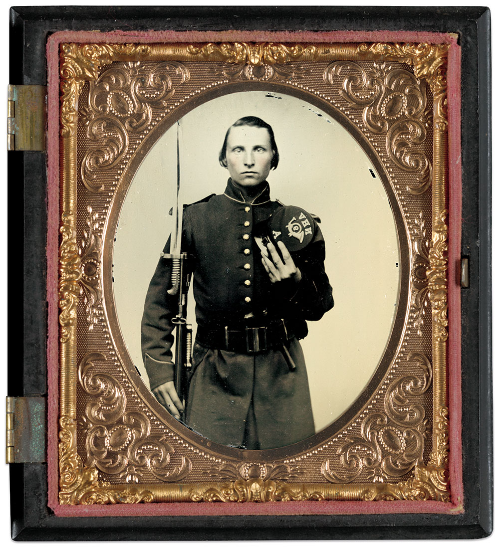 """Charles M. Judson from Kingston in Rockingham County, N.H., mustered in as a private in Company A of the 9th New Hampshire Infantry on July 3, 1862. Photographed at Camp Colby before his regiment left for the front, he has brass shoulder scales attached to his regulation frock coat. The brasses on his cap top have the letters """"NHV"""" above a militia pattern infantry horn with regimental numeral """"9"""" within the loop, and company letter below. He holds a Model 1855 rifle with a saber bayonet attached, and has a revolver of unknown pattern tucked into a riflemen's belt. A second sword bayonet in his scabbard indicates his long arm was likely a photographer's prop. A note inside the case with the image includes his name and location, and that this photograph was presented to his sister, Addie. Sixth plate ambrotype by an anonymous photographer. The Liljenquist Family Collection at the Library of Congress."""