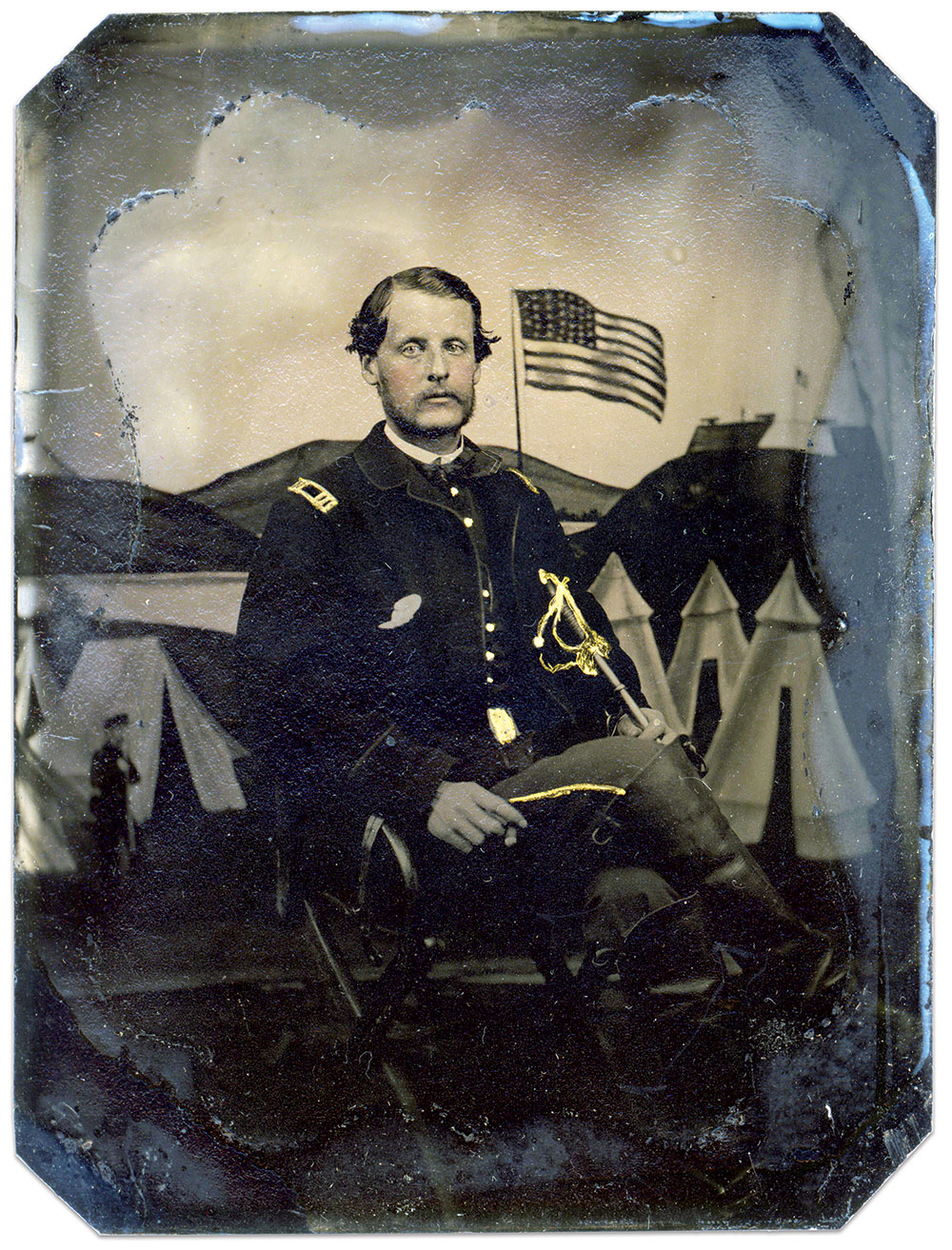 """THE STAR-SPANGLED BANNERpainted into the backdrop includes 35 stars in an uncommon arrangement of columns of five and six stars with two stars on the far left of the canton. The captain seated in front of it is Francis Bedell """"Frank"""" Allibone of Company B of the 1st New Jersey Cavalry. Allibone barely survived the surrender at Appomattox, dying after a fall from his horse on May 9, 1865, at Petersburg, Va. Quarter-plate tintype. Andrew German Collection."""