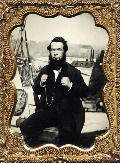 Photographer Enoch Long with his wellknown backdrop. Quarter-plate ruby ambrotype.Mike Medhurst collection.