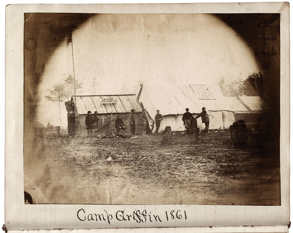 """The """"Picture Gallery"""" at Camp Griffin, near Lewinsville, Va., was operated by George H. Houghton, of Brattleboro, Vt. He followed the volunteers from his home state to war in 1861. Houghton stayed with the Vermont Brigade during the winter of 1861-62, and joined them again later in 1862. The timber-built cabin with the """"Picture Gallery"""" sign probably served as his gallery and sales room, while his studio would have been in the larger tent, which typically has a sky-light in its roof. Library of Congress."""