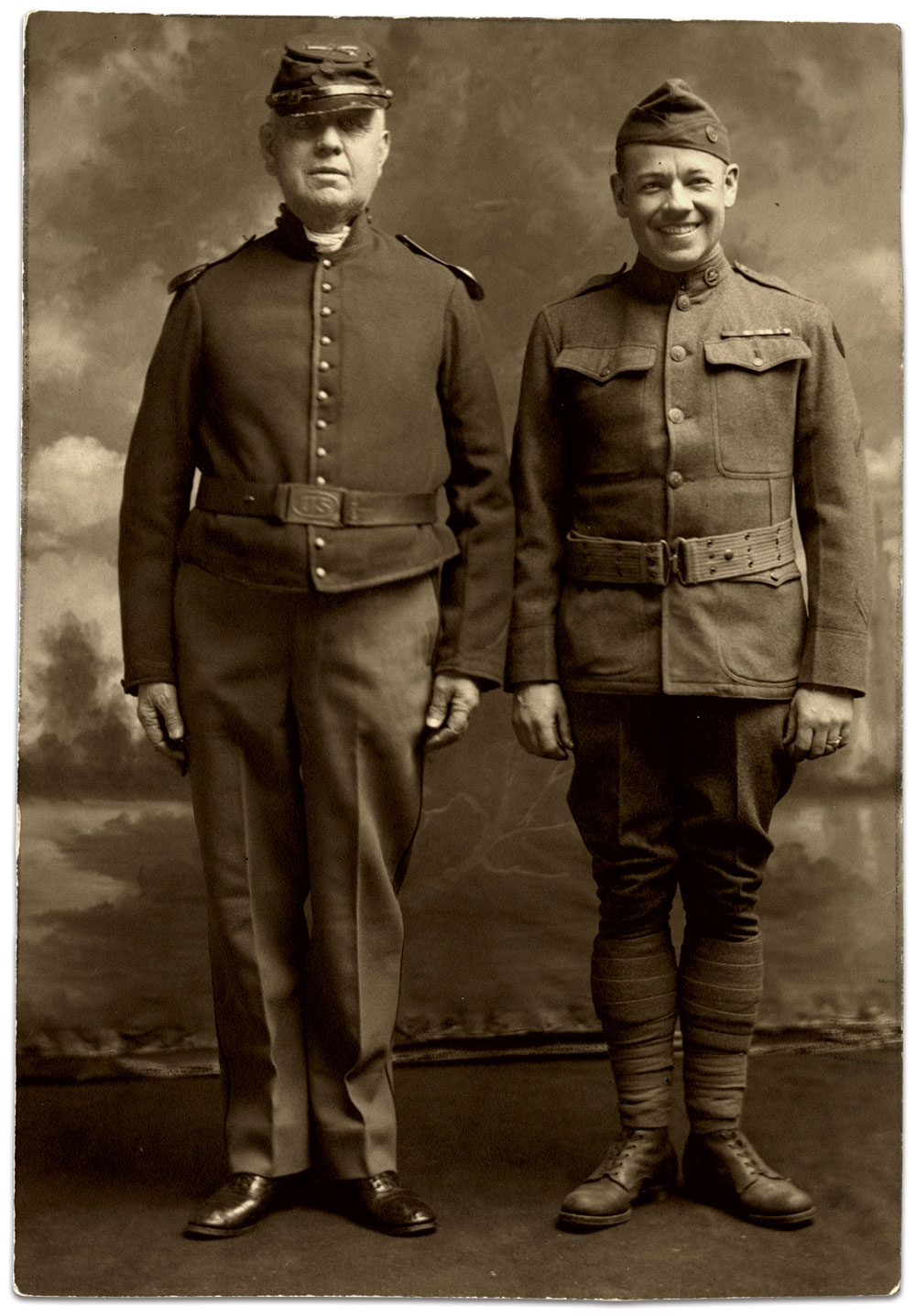 Father and son pose together in this World War I era image. Jeremiah Lockwood wears his original Civil War cap, as evidenced by tattered visor, and a hybrid uniform that is likely army surplus. His son Robert's uniform sleeve has overseas chevrons, which suggests this portrait was taken after his return from Europe in 1919. Real photo postcard by an anonymous photographer.