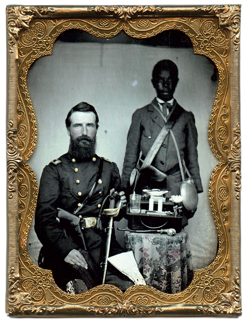 Watson and a personal attendant posed for this portrait during the major's enlistment with the 6th in 1861. Watson sits with his Model 1851 staff and field sword, holstered revolver, and thick braided cord, likely a pocket watch chain, extending from the slash pocket of his uniform coat to a button on his double-breasted frock coat. The attendant, his name unknown, stands behind Watson. He wears a civilian coat, holstered revolver, canteen with fabric sling and a haversack that appears to be constructed from rubberized material instead of the more common tarred weatherproofing treatment. On the table between the two men sits a hinged carrying case, its trays opened to reveal a pair of candles with unlit wicks, a drinking glass, plate, tin box, corkscrew, and eating utensils. The napkin on Watson's knee compliments the contents of the case. A pipe with wood bowl and cap and curved stem completes the picture. Quarter-plate ambrotype by an unidentified photographer. Author's collection.