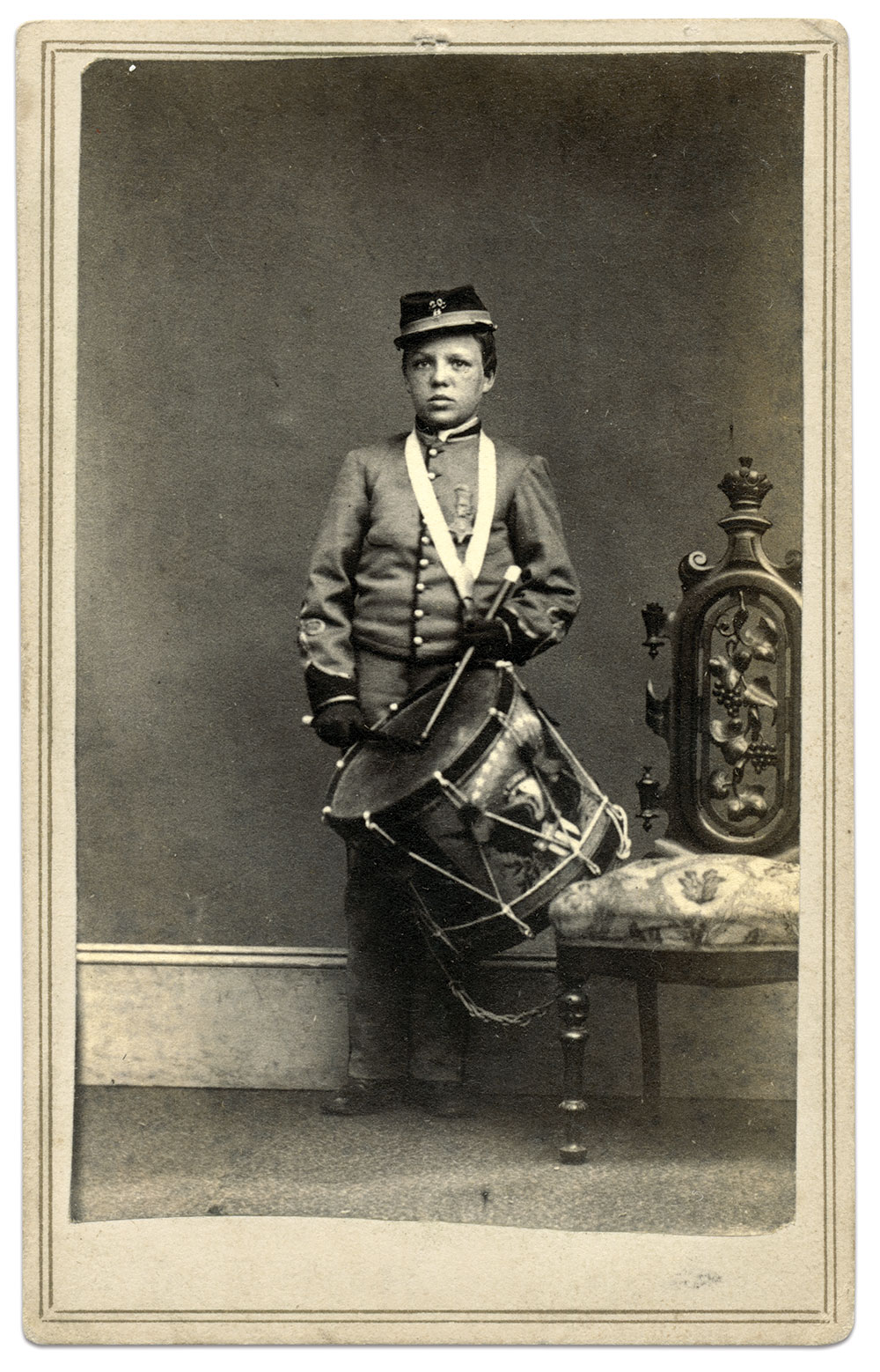 """Willie Johnston is pictured in this carte de visite as a Veteran Reserve Corpsman with his drum and Medal of Honor. Marius B. Peladeau, author of the 2005 book When Willie Went to War, observes that the drumsticks appear to be expensive, perhaps topped by German silver or ivory. Though the photographer of this portrait is unidentified, a February 1864 report in The Caledonian newspaper of St. Johnsbury, Vt., states """"Willie Johnston, the little drummer boy, returned to his regiment last week. Mr. Gage has card pictures of this little veteran with his drum, for sale."""" Mr. Gage is likely St. Johnsbury photographer Franklin B. Gage. Carte de visite attributed to Franklin B. Gage of St. Johnsbury, Vt. Ronald S. Coddington Collection."""