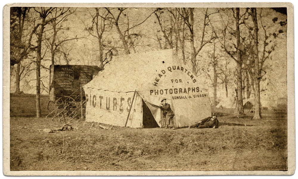 A meetup of two Cincinnati-based camp photographers in the field is captured in this circa 1864 carte de visite. Front and center is the tent studio of photographers Bonsall and Gibson. The two men pictured may be them. The wagon parked behind the tent is covered in advertising for photographer Charles Waldack. Isaac H. Bonsall worked for a time as a photographer for the 14th Corps of the Department of the Cumberland. Gibson is likely Henry S. Gibson, who partnered with photographer Julius E. Dewey in 1863. Waldack, a Belgium native, specialized in outdoor photography. He may have been the man behind the camera for this image. Carte de visite by Dewey & Gibson of Cincinnati, Ohio. Liljenquist Family Collection, Library of Congress.