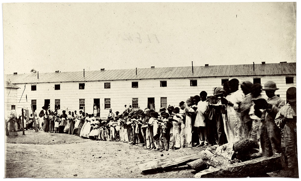 """The caption for this photograph printed in They Knew Lincoln states that these freedmen were waiting to sing for President Lincoln, and credited Mathew Brady as the photographer. Two similar images in the Library of Congress describe the location as the Freedmen's Village in Arlington, Va., and the Freedman's barracks in Alexandria, Va. The Library also references two variant descriptions: A contraband school (National Archives) and """"residents of Camp Barker as they prepared for Lincoln's visit"""" (The White House Historical Association). Albumen print by an anonymous photographer. Library of Congress."""