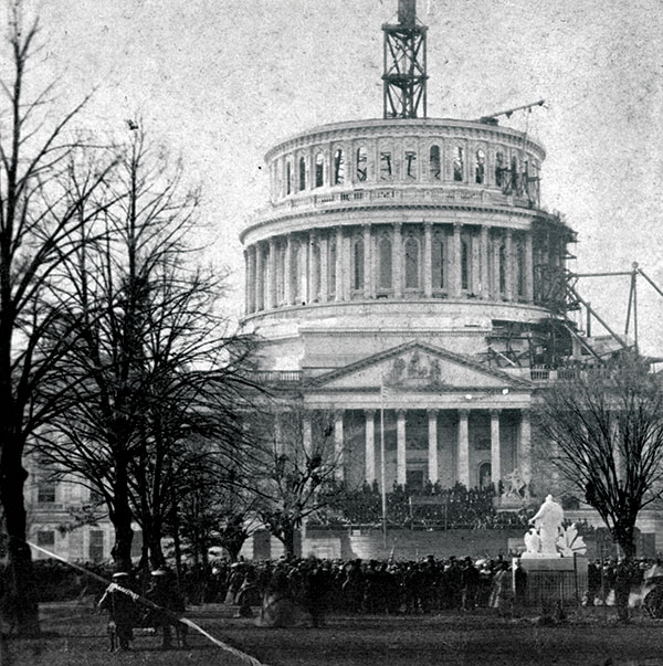 THE CAPITOL IN 1861: The unfinished dome as it appeared during the inauguration of Abraham Lincoln on March 4, 1861.  Maj. Watson and his comrades slept in the Senate Chamber after their arrival. The regiment spent much time during the days immediately following its arrival fortifying the building and grounds from assault. Salted paper print by an unidentified photographer. Library of Congress.