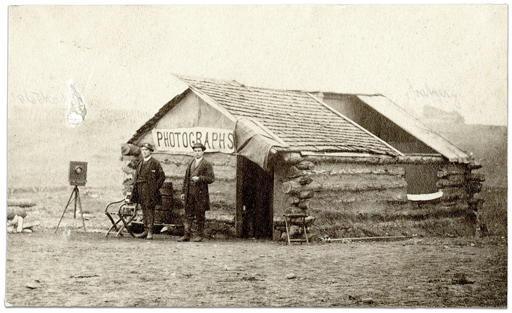 The makeshift studio of the Bergstresser brothers was photographed while they were encamped near the 3rd Division, Fifth Army Corps, Army of the Potomac, at City Point, Va., circa 1863-64. A whole section of the shingle roof of the log-built structure could be slid along to allow the sunlight in. Also note the cloth blackout over the door and window. Standing to their left is one of their cameras on a tripod. Three brothers were active in the business: A.J., J.L. and S.L.  The most prominent appears to have been Stewart L. Bergstresser, a daguerreotypist in the early 1850s. Unmounted carte de visite by the Bergstresser Brothers of Pennsylvania. MOLLUS Collection, U.S. Army Heritage and Education Center.