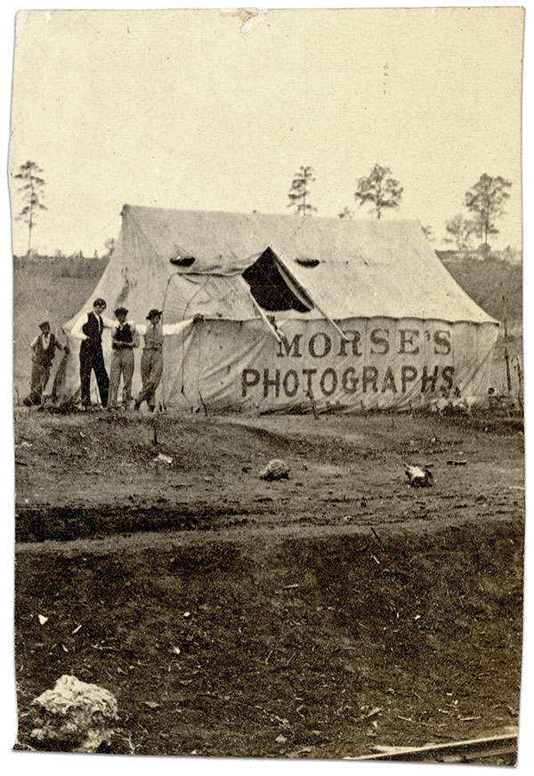 """Operating the """"Gallery of the Cumberland"""" at 25 Cedar Street in Nashville, Tennessee, Algenon S. Morse, with partner William A. Peaslee, often took his """"traveling tent"""" into nearby military encampments. Pitched at Camp Jenkins near Chattanooga, in Lookout Valley, during the winter of 1863-64, his tent has a large canvas flap folded back in its roof to admit sufficient light to the studio area. Prospective customers could hardly fail to see the two-feet high """"MORSE'S PHOTOGRAPHS"""" painted on its sidewall. Unmounted carte de visite by Morse and Peaslee of Nashville, Tenn. Military Order of the Loyal Legion of the United States Collection, U.S. Army Heritage & Education Center, Carlile Barracks, Pa."""