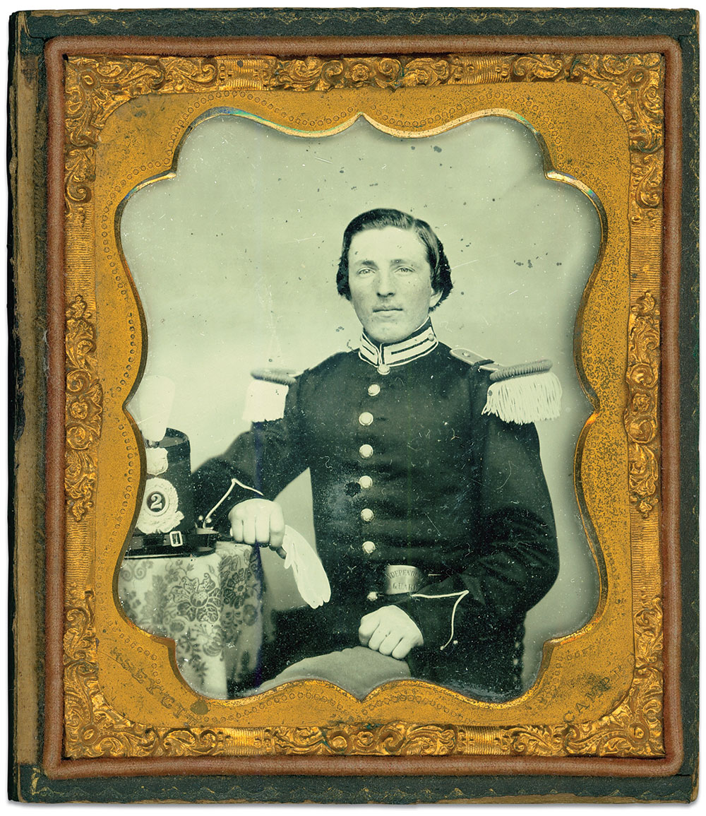 """Peter H. Hoyt of the """"Independent Guard"""" of the 2nd Regiment Foot Militia of the State of New Jersey. In 1861, he became 1st lieutenant of Company K, 2nd Regiment Militia, or the 18th New Jersey Infantry. Here, he wears his pre-war enlisted uniform of dark blue coat, light blue trousers and white trim. His company designation appears on his waist belt plate. Sixth-plate ambrotype by Campbell of Jersey City, N.J. Author's collection."""