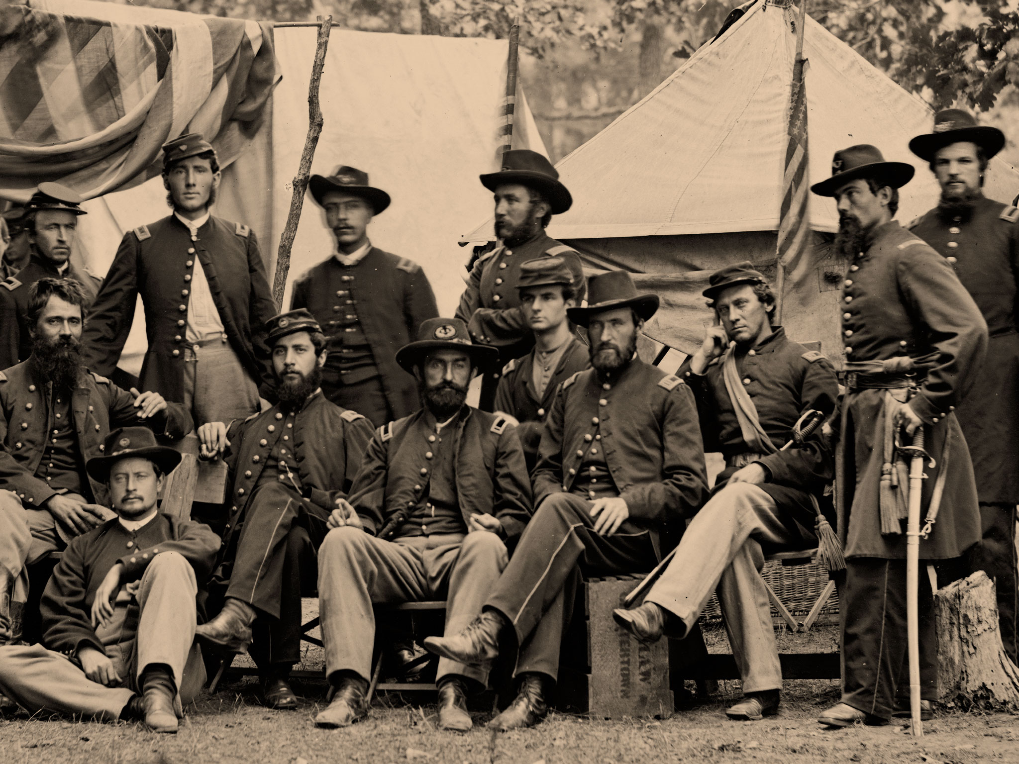 """Detail of an image by Timothy O'Sullivan of """"Officers of the 93d New York Infantry"""" shows Ball standing in the center with arms folded. Capt. Barnes sits on a wooden box with his legs crossed. Library of Congress."""