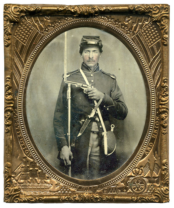 SHEATHED KNIFE IN BELT. Prop: NO. Details: The sheath that holds this Union soldier's knife, left, is clipped to his waist belt, a strong indicator that the soldier carried or intended to carry it with him in the field. His revolver, by contrast, appears not to have a holster. It may be hidden from view or perhaps carried in a pocket. It is also possible that the revolver may have not belonged to him. Sixth-plate tintype by an anonymous photographer. Brian Boeve collection.