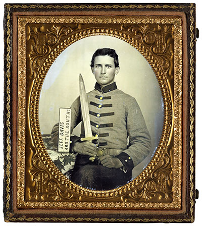 """""""JEFF DAVIS AND THE SOUTH!"""" SIGN: Prop: Yes.Details: Henry Augustus Moore, a private in Company F of the 15th Mississippi Infantry, poses with a placard that leaves no doubt where his loyalties lie. Prop signs are rare in period photographs. The artillery short sword he holds may also be a prop.  Sixth-plate ambrotype by an anonymous photographer. Liljenquist Family Collection, Library of Congress."""