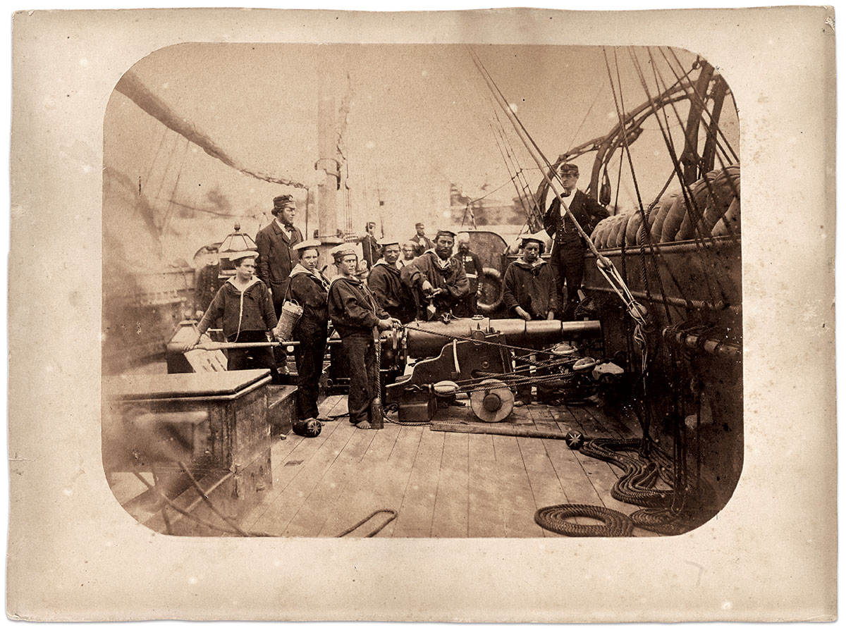 Gault captures a British crew: Officers and men pose on the deck of H.M.S. Nimble in 1863. A five-gun, wooden Philomel-class vessel of the British Royal Navy, the Nimble served in the North America and West Indies Station as a tender to H.M.S. Nile. The Nimble operated between Halifax and Bermuda during the Trent Affair in November 1861. The vessel and crew went on to participate in a 4-week, quasi-diplomatic trip to New York City in September 1863. Mounted albumen by S.W. Gault. Courtesy of the Bermuda Historical Society, Bermuda Archives, Hamilton, Bermuda.