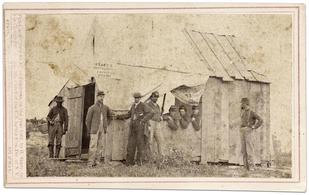 """This wooden shack near Fortress Monroe on the Virginia Peninsula was home to """"Stacy's Photographic Ambrotype Rooms"""" in the summer of 1861. The proprietor, George Stacy, operated a studio in New York City beginning in 1859. He may be standing third from left. The canvas of a wall tent covers his skylight and three prospective customers waiting inside. Carte de visite by George Stacy of New York City. Liljenquist Family Collection, Library of Congress."""