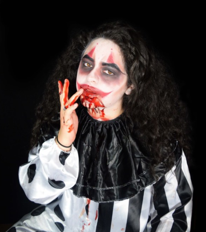 Kenya Tovar licks fake blood from her fingers to heighten the sense of creepiness of her clown costume. Photo by Robert Spencer.