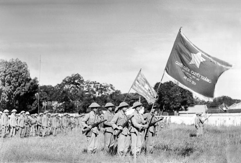 """Una unidad con la bandera """"Quyet chien, quyet thang"""" (en idioma vietnamita significa """"perseguir el combate a ultranza y estar decidido a vencer"""") condecorada por el Presidente Ho Chi Minh, asiste al histórico acto de saludo a la bandera nacional. (Fuente: VNA)"""
