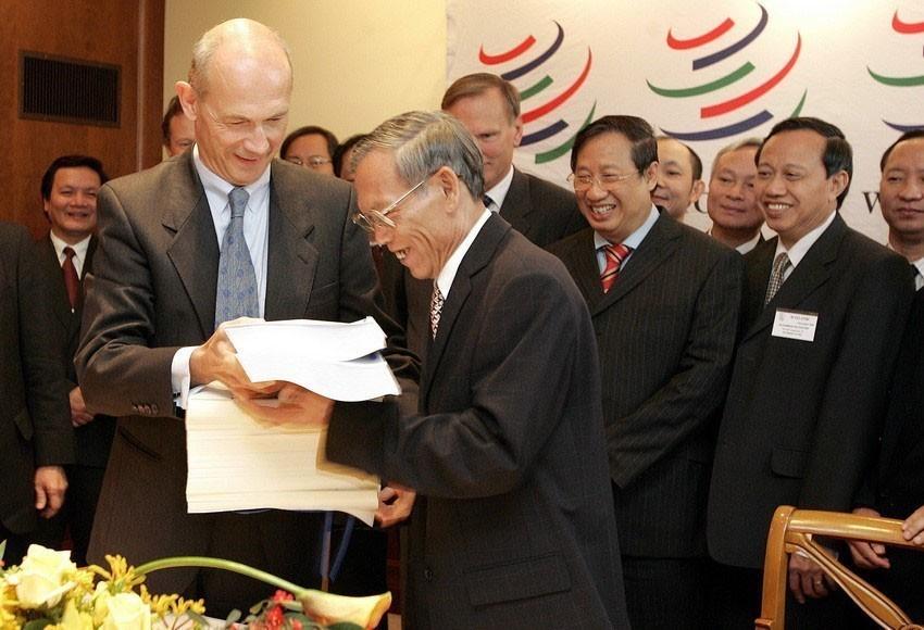 Tổng Giám đốc WTO Pascal Lamy trao các văn kiện về việc kết nạp Việt Nam trở thành thành viên chính thức thứ 150 của WTO cho Bộ trưởng Thương mại Việt Nam Trương Đình Tuyển, tại buổi lễ kết nạp Việt Nam vào WTO, ngày 7/11/2006, tại trụ sở WTO ở Geneva (Thụy Sĩ). (Nguồn: AFP/TTXVN phát)