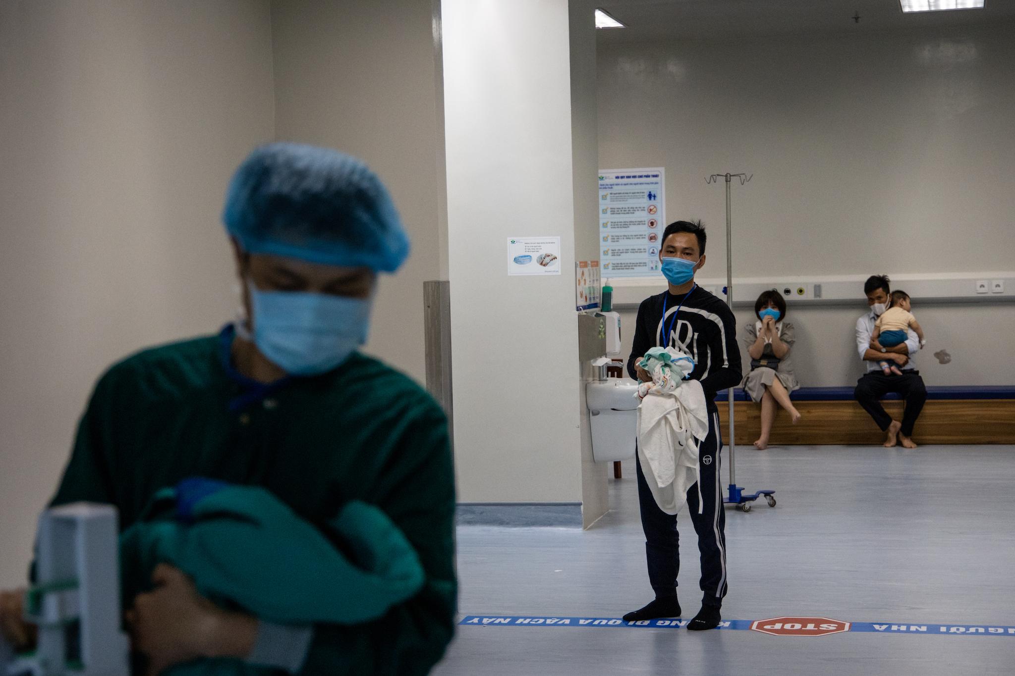 Anh Lượng quyến luyến đứng nhìn con trai mình trước phòng phẫu thuật. Chỉ ít phút nữa thôi, bé Quốc Thiên sẽ bước vào cuộc chiến