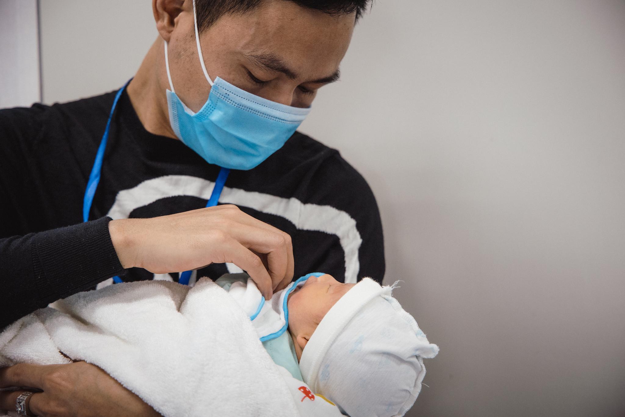 Anh Lượng lặng thinh bên cậu con trai bé nhỏ. Anh liên tục động viên và an ủi con mình. (Ảnh: Minh Sơn/Vietnam+)