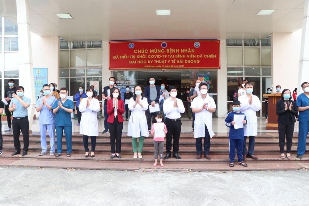 Các y bác sỹ chúc mừng 27 bệnh nhân đã khỏi bệnh và được ra viện tại tỉnh Hải Dương ngày 26/2. (Ảnh: Mạnh Minh/TTXVN)